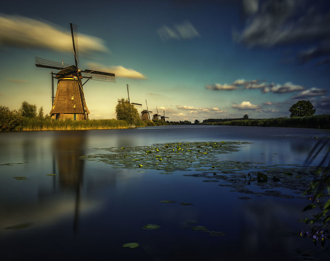 Scenic view of windmills by lake against sky