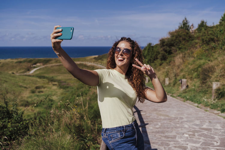 Young woman photographing on mobile phone