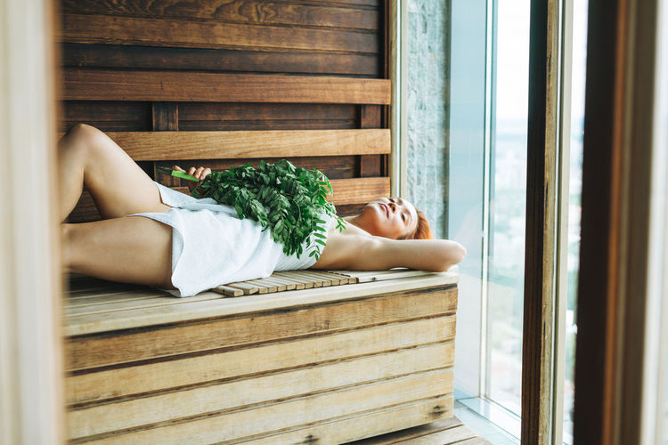 Young woman in white towel lies on wooden shelf in sauna with rowan broom in spa hotel
