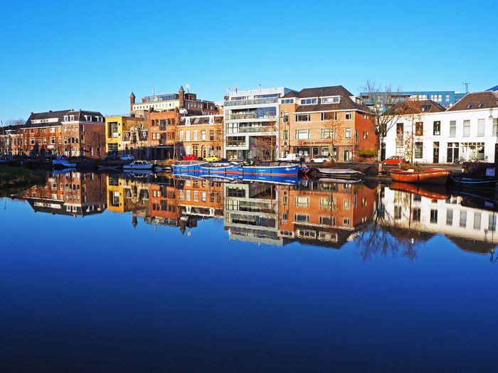 Reflection of buildings in canal against blue sky