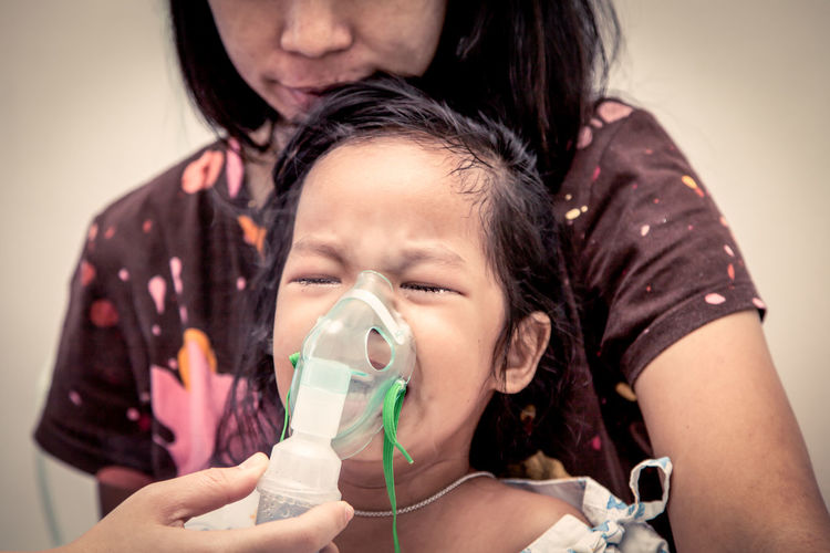 Cropped Image Of Doctor Putting Mask On Crying Girl