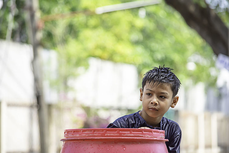 Boy looking away by wet barrel against trees