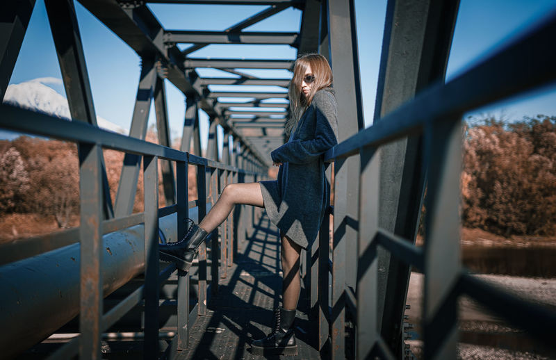 Woman seen through railing on bridge