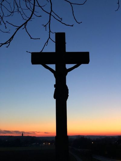 Silhouette cross against clear sky during sunset