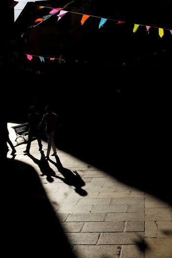 Shadow of people on illuminated floor in city at night