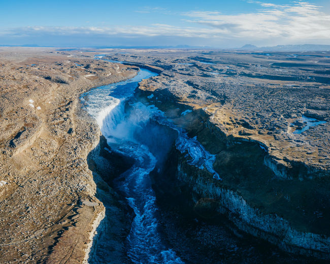 Aerial view of river flowing through land against sky