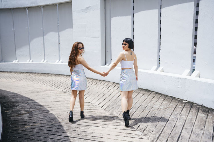Full length portrait of lesbian couple holding hands while walking outdoors