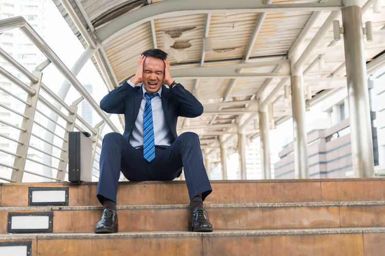 Full length of frustrated businessman sitting on steps
