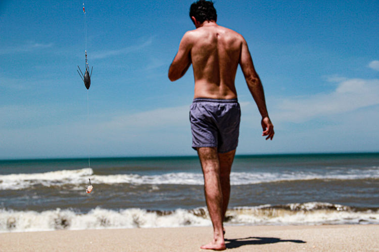 Rear view of shirtless man walking on beach