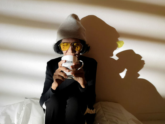 Senior woman drinking coffee while sitting against wall at home