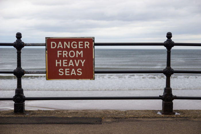 """Sign saying """"Danger from heavy seas"""" on a railing at the waterfront on GB Danger Sign SignSignEverywhereASign Signs Communication Danger Horizon Over Water Nature Outdoors Railing Text Warning Warning Sign"""
