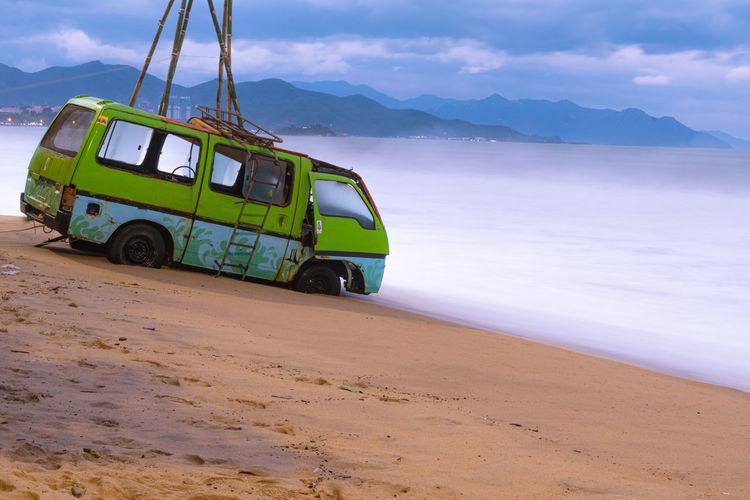Vintage car on beach against sky