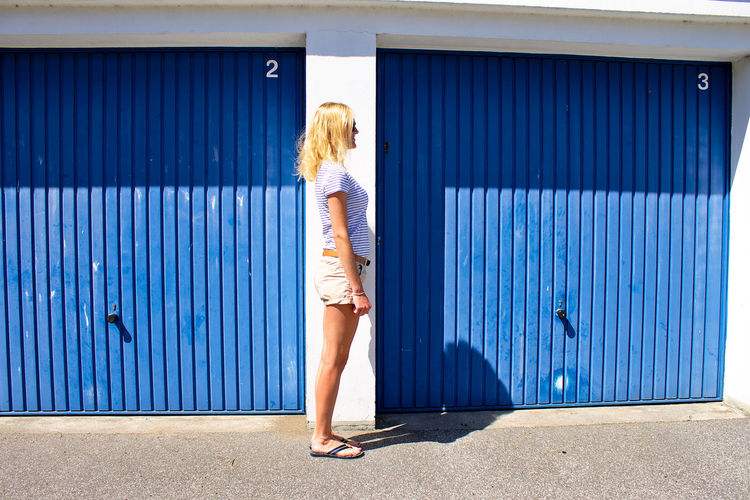 Woman standing against blue wall