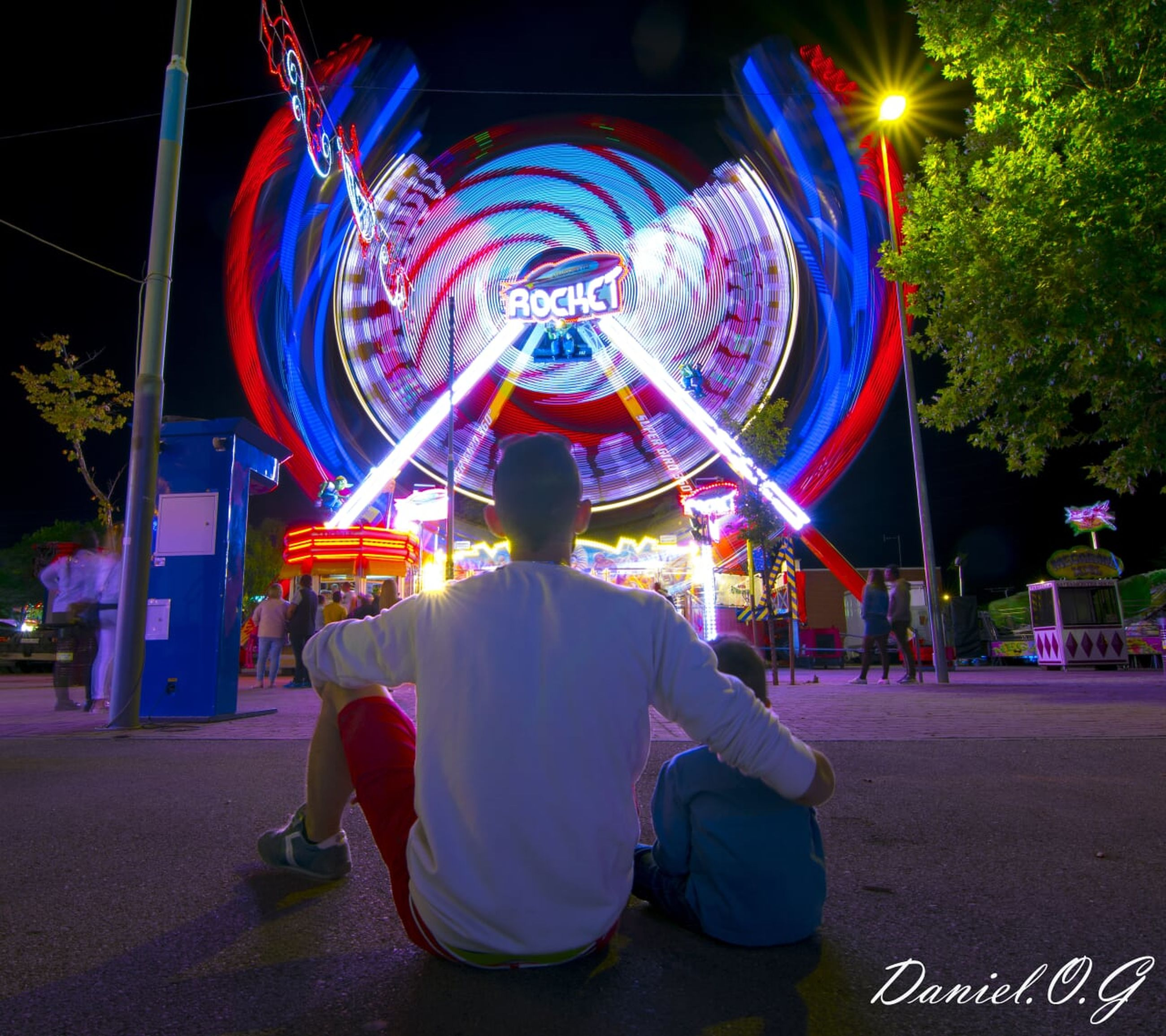 illuminated, real people, multi colored, men, night, one person, lifestyles, rear view, arts culture and entertainment, long exposure, motion, glowing, leisure activity, amusement park, spinning, amusement park ride, casual clothing, blurred motion, sitting, light