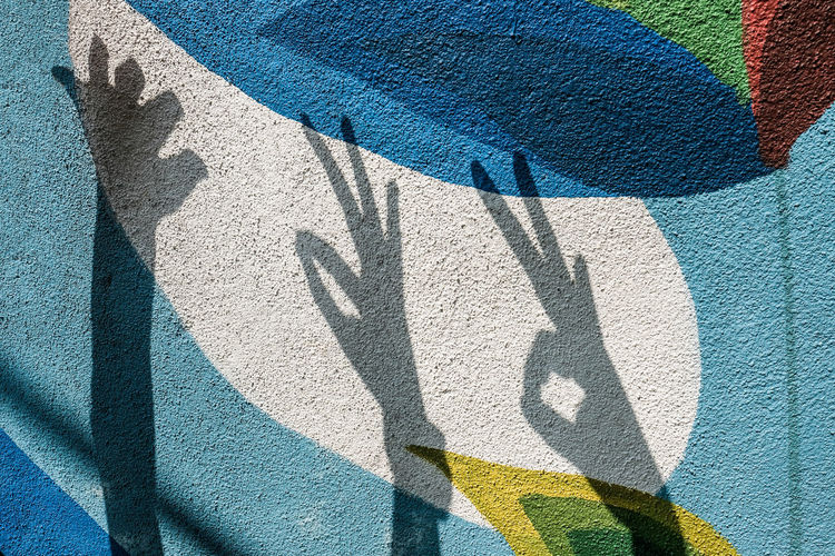 Shadow of hands on painted wall