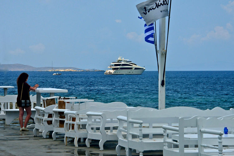 yacht anchored and a woman looking at it from the land in a bar Water Sea Sky Nautical Vessel Transportation Horizon Mode Of Transportation Nature Real People Horizon Over Water Day People Travel Leisure Activity Scenics - Nature Flag Beauty In Nature Women Outdoors Mykonos,Greece Yacht Seascape White Furnitures Cruising Summertime Looking The Horizon