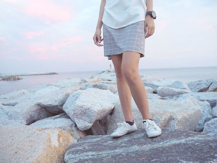 Low section of woman standing on rocky beach