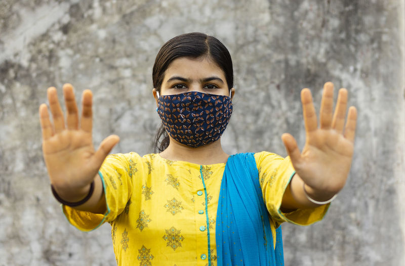 Indian woman showing open palm or stop gesture and looking at camera with nose mask on