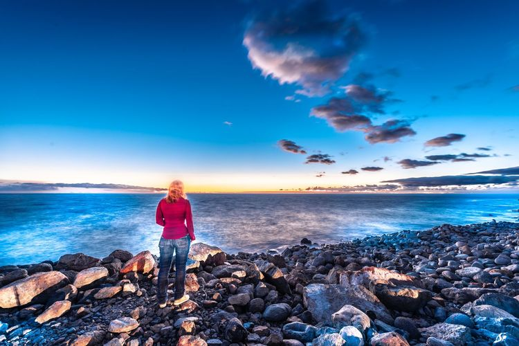 Woman standing on rock by sea against blue sky