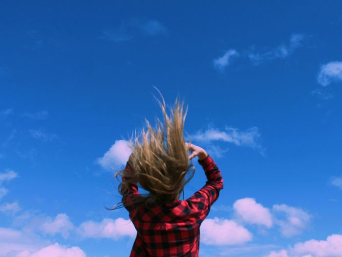 Low angle view of woman tossing hair against sky