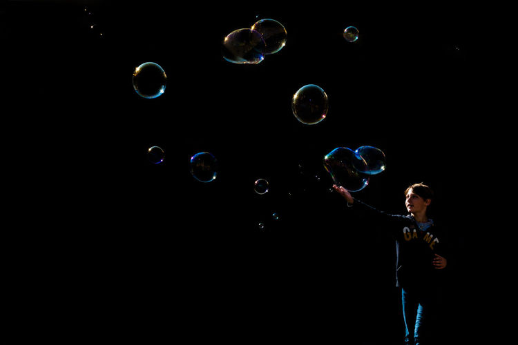 Man touching bubbles while standing against black background