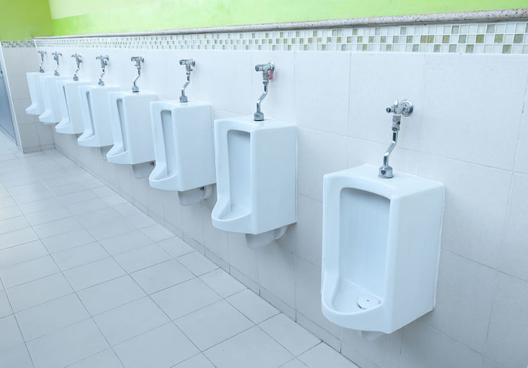 Absence Architecture Bathroom Built Structure Clean Day Flooring Hygiene In A Row Indoors  No People Public Building Public Restroom Repetition Seat Side By Side Tile Tiled Floor Toilet Urinal Wall - Building Feature White Color
