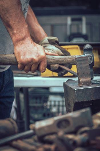 Midsection of man hammering metal on anvil in workshop