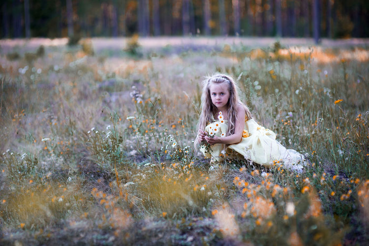 Portrait of cute girl collecting flowers from field