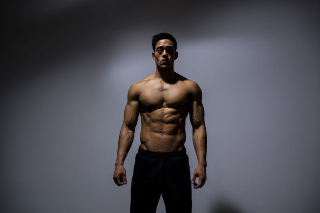 A male fitness model displaying his chiseled physique. Adult Asian  Front Facing Human Body Man Shirtless Vietnamese Abdominals Abs Chiseled Fitness Fitness Model Fitness Training Grey Wall Male Medium Shot Model Muscles Muscular Build Pectoral Physique  Posing Powerful Six Pack Strong
