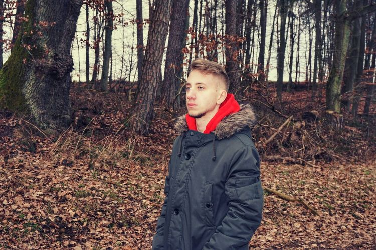 Young man looking away while standing in forest during autumn