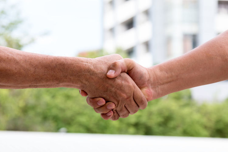 Adult Adults Only Agreement Architecture Bonding Close-up Connection Cooperation Day Focus On Foreground Friendship Greeting Handshake Human Body Part Human Hand Men Outdoors Partnership - Teamwork People Real People Teamwork Togetherness Two People Unity