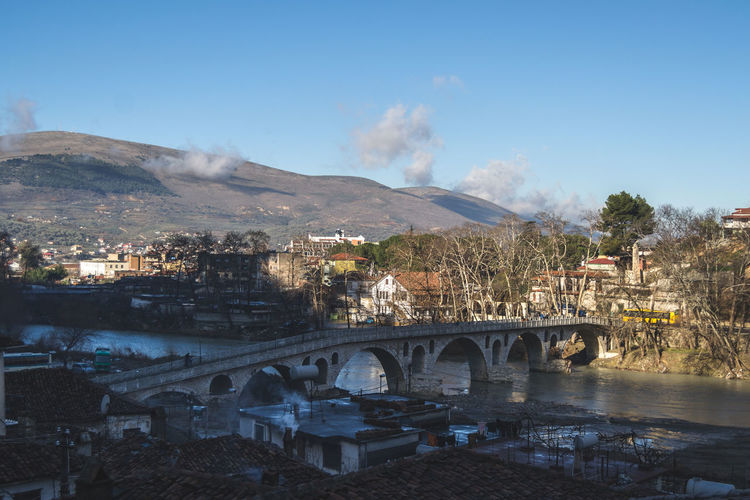 Bridge over river in town against sky