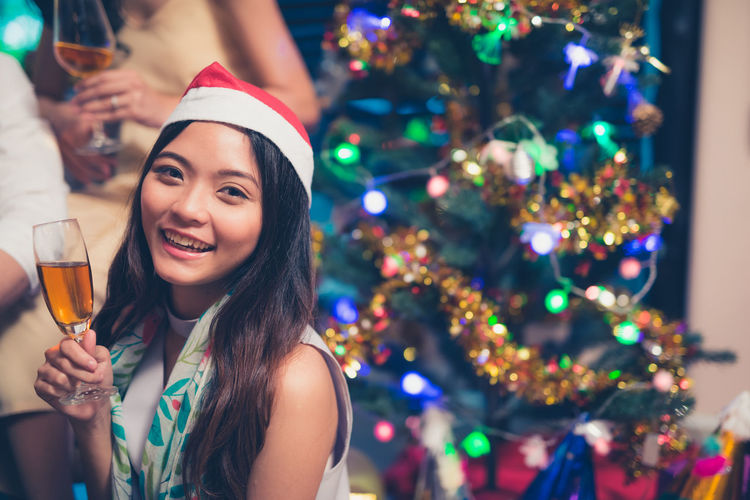 Portrait Of Young Woman Holding Drink At Christmas Party