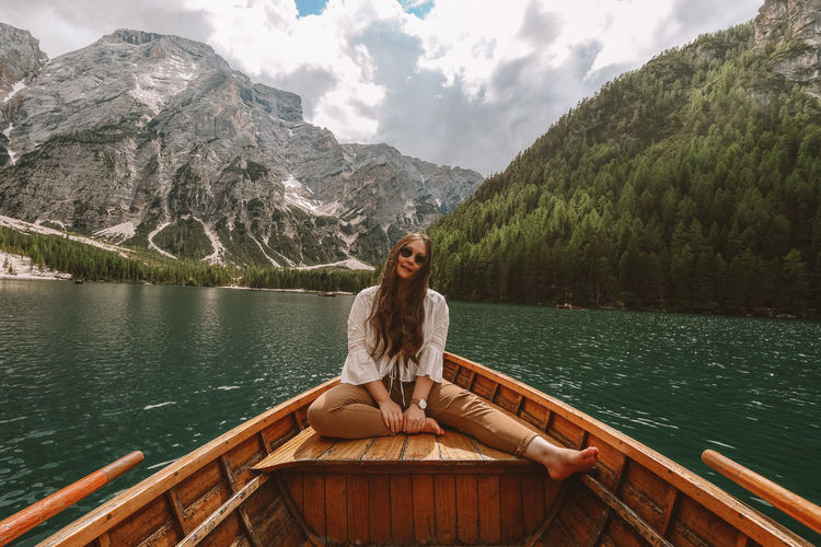 Full length of young woman in lake against mountains