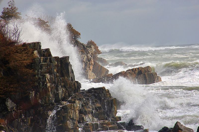 Waves splashing on rocks against sky