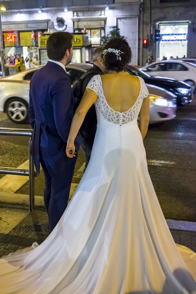 Bride and Groom in Gran Via Madrid during a photo shoot. City Life City Street Couple Taking Photos Traffic Wedding Bride Groom Life Events Love Men Night People Real People Rear View Standing Street Togetherness Two People Wedding Wedding Day Wedding Dress Well-dressed White Women