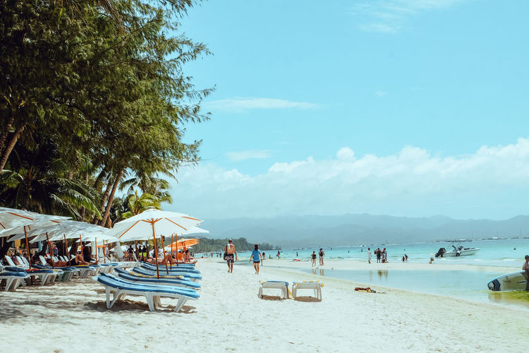 People at beach against sky at boracay during summer