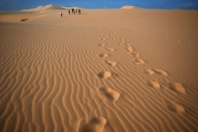 Distance shot of people walking at desert with footprints in foreground