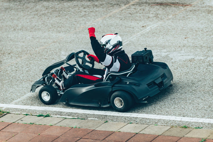 Woman Driving Go-Cart Go-carting Carting Champ Car Racing Soapbox Chart Chart Car Competitive Sport Motorsport Driver Drive Speed Sport Sport Race Motor Racing Track Activity Young Woman Driving Sports Uniform Sports Helmet Lifestyle Car Racing Fun Arm Raised Victory