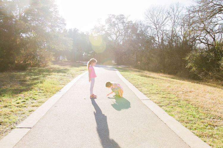 Full length of girl looking at sister drawing on footpath in park against trees