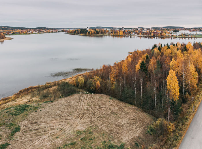 High angle view of lake amidst trees against sky