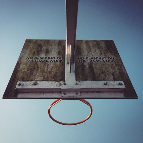 Low Angle View Of Basketball Hoop With Text Against Blue Sky