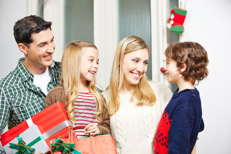 Cheerful Family Holding Christmas Gifts While Standing At Home