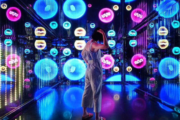 Full length of woman touching illuminated lighting equipment