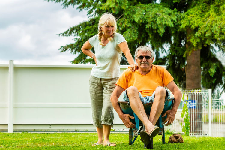 Senior man sitting on wheelbarrow while standing with wife at yard