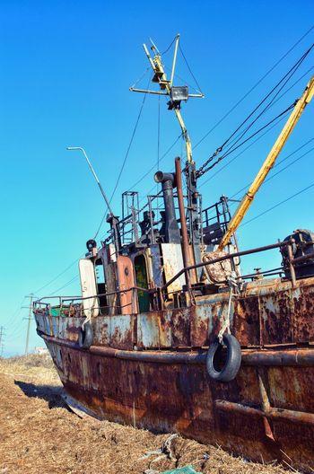 Damaged boat on land against clear blue sky