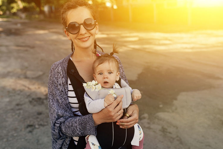 Portrait of happy mother carrying daughter while standing outdoors during sunset
