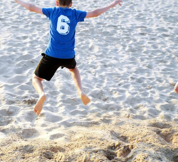 High angle view of boy jumping on shore