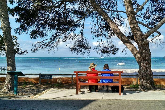 Two women on a seaside park bench. Seaside Hanging Out Streetphotography Beach Parkbench Ocean Scene Idyllic Tranquil Scene