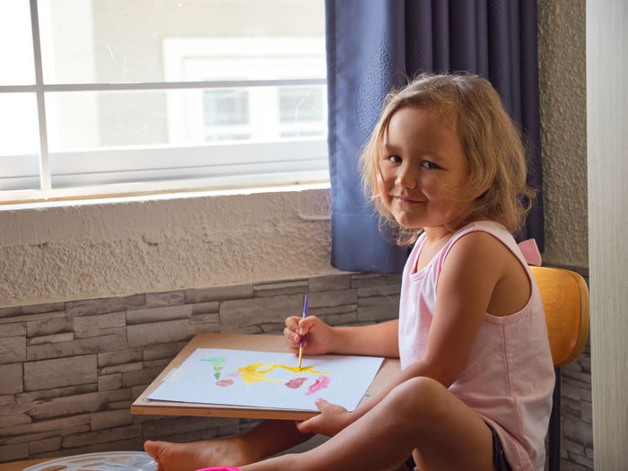 Side view portrait of girl drawing on paper while sitting on chair at home